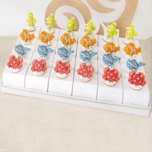 Torta bomboniera composta da set 24 tappi in sughero realizzati in resina. I tappi sono applicati a scatoline portaconfetti colorate con animaletti marini, in 4 decorazioni, cavalluccio marino verde, granchio rosso, pesce arancione e balena azzurra.