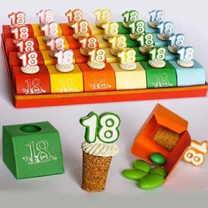 Bomboniera 18 anni composta da set 24 tappi in sughero realizzati in resina. I tappi sono applicati a scatoline portaconfetti colorate con su il numero 18 con contorni in vari colori assortiti: rosso, giallo, arancione, verde, rosa e celeste. Misura tappo: 6.5 cm. (di cui: 3 cm. sughero e 3.5 cm. oggettino).