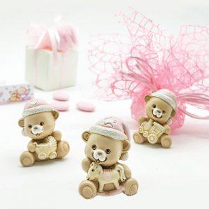 Bomboniere battesimo bimba orsetti ideali anche come nascita realizzati in resina colorata. Questi simpatici orsetti sono assortiti in tre forme come dimostrato in foto (cavalluccio, trenino, culla)