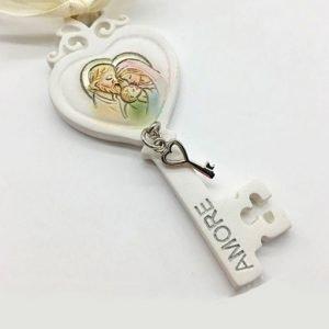 Bomboniera chiave sacra famiglia a forma di cuore, realizzata in resina decorata da un ciondolino in metallo a forma di chiave rappresenta la Sacra Famiglia. Nuova collezione 2019.