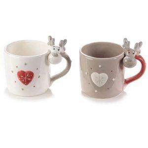 Set tazze di Natale realizzate in ceramica con renna e decoro a cuore in rilievo. Il prezzo si riferisce al set di due tazze di capacità 350 ml. Misura: 9x8,5 cm.