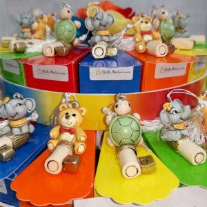 Torta bomboniere compleanno assortita con tre modelli (chiavi portafortuna tartaruga, elefantino, orsetto) realizzate in resina colorata.