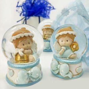 Bomboniera battesimo angioletto palla di neve di vetro con neve glitterata. Bomboniere in resina lucida bianca e celeste con fiocchetto sulla base. Le palle di neve sono assortite in tre varianti di modello: assortita in 3 varianti, con campana, quadrifoglio e stella