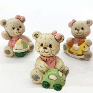 Bomboniera orsetto bimba realizzata in resina effetto legno: la resina infatti è lavorata con lievi intagli, che richiamato le venature tipiche del legno. Orsetto assortito in 3 modelli: con barchetta, macchinina e cavallo a dondolo.