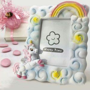 Portafoto unicorno bimba realizzato in resina decorato in modo da sembrare ricoperta da soffici nuvole bianche, con stelline ed un arcobaleno, in alto a destra. Nell'angolo opposto, è raffigurato l'elegante unicorno con ali, criniera, coda e zoccoli rosa, specifica per bimba.