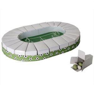 Torta bomboniera stadio calcio realizzata in cartoncino con base verde decorata da palloni da calcio e fette portaconfetti bianche. Al centro della torta un campo da calcio con porte in metallo.