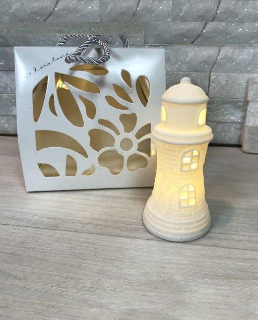 Bomboniera Faro led Claraluna realizzata in porcellana. Elegante bomboniera faro ideale per tipo di evento. Compreso nel prezzo regaliamo shopper led.