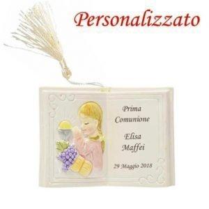 Bomboniera libro comunione, realizzato in resina, bambina con calice in preghiera con personalizzazione sulla pagina destra, con nappina panna come illustrato in foto.