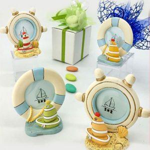 Bomboniera portafoto mare realizzato in resina assortiti in due forme, timone e salvagente, ed in 4 modelli con barchette assortite in diversi colori ed impreziosite da strass.