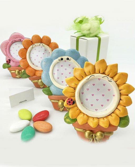 Bomboniera portafoto fiore realizzato in resina a forma di vaso con fiocco color oro al di sopra del quale è posto un grande delizioso fiore, assortito in 4 tipologie