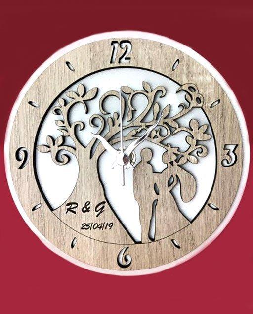 Orologio coppia sposi personalizzabile realizzato in legno bianco e tortora, con raffigurazione di unalbero della vita con sposi stilizzati.