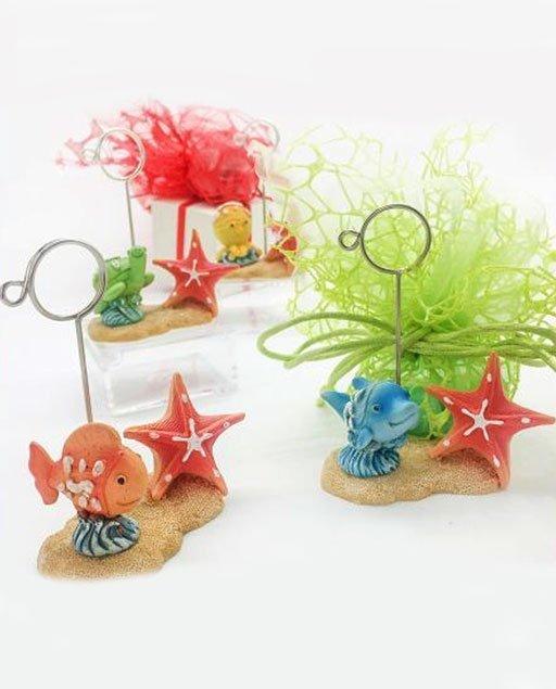 Memoclip pesciolini realizzati in resinacomposti da una base che rappresenta un cumulo di sabbia, su cui è posata unastella marina color corallo accanto alla stella