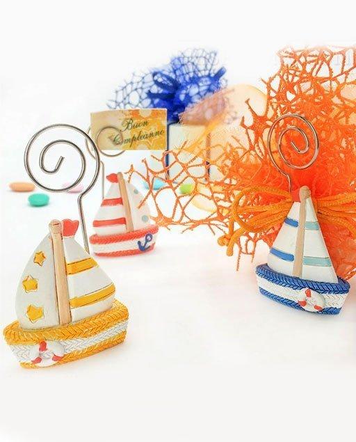 Barchetta bomboniera memoclip realizzata in resina colorata, assortiti in 3 differenti e di colori diversi, come dimostrato in foto. Bomboniere utili come particolari portafoto tema mare.