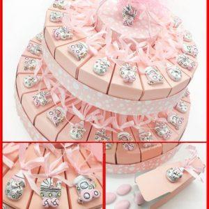 Torta portachiavi Baby rosa a 18 fette. Su ogni fetta è applicato un appendino in resina argentata raffigurante 3 diversi soggetti: biberon, trenino e passeggino.