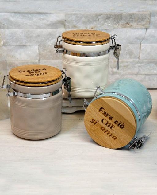 Bomboniera utile Barattoli colorati realizzati in ceramica ,di forma cilindrica dotati di tappo in legno incisa una frase