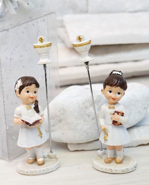 Bomboniera prima comunione bambina in resina, con abiti eleganti prima comunione, sulla base rotonda, oltre che la statuina in resina, è presente l'asta con spirale/clip per bomboniere utili come portafoto e portamemo