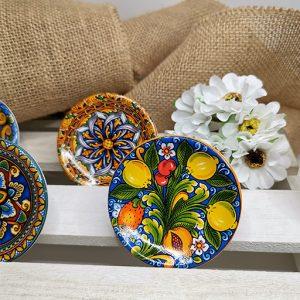 Magnete Piattino in ceramica siciliana di caltagirone. Decorati in 4 piattini diversi, come illustrato in foto. I nostri piatti si ispirano allacultura siciliana, ai suoi colori e ai suoidecori tipici Siciliani. Ideale per ogni cerimonia.