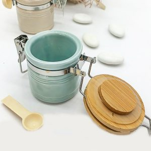 Bomboniera utile Barattoli con cucchiaio colorati realizzati in ceramica ,di forma cilindrica dotati di tappo in legno incisa una frase