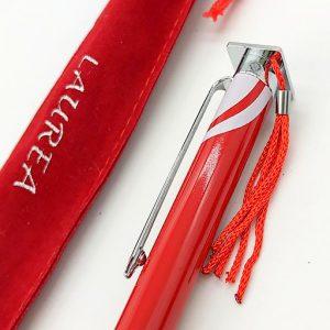 Penna biro elegante laurea con cappellino sulla punta e nappina, ( comprensiva di custodia in velluto ), cosi come illustrato in foto.