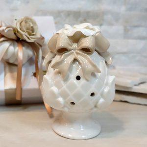 Bomboniera pumo tortora realizzato in porcellana di colore bianco fiocco tortora. ll pumo in porcellana è un pregiato elemento decorativo, simbolo portafortuna.