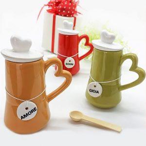 """Zuccheriera Moka realizzata in ceramica lucida e colorata, assortita in tre colori moderni: arancio, verde, rossa. Manico a forma di cuore e medaglietta in ceramica bianca con scritta """"Amore"""", """"Sogni"""" e """"Gioia"""