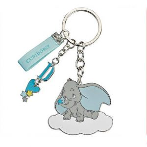 """Portachiavi Disney Dumbo, realizzato in metallo. Oltre al ciondolo Dumbo, ci sono altri charms: uno con lettera """"D"""" azzurra, a cui è legato un cuoricino celeste con stelline e l'altro in stoffa azzurra con scritta """"Dumbo""""."""