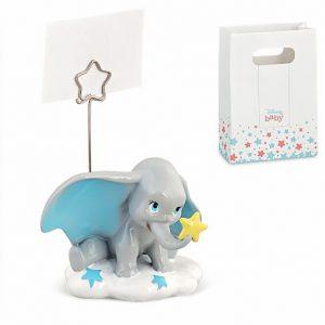 Memoclip Dumbo Disney, bomboniera realizzata in resina,Dumbo raffigurato seduto su una nuvola con stellina sulla proboscide e orecchio all'insù e asta in metallo con terminale a forma di stella in cui inserire bigliettini e foto bambini.