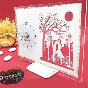 Bomboniera orologio matrimonio, di forma rettangolare, realizzato in vetro decorato: il vetro è dipinto in bianco ed in trasparenza raffigurano una coppia di innamorati in bici e sullo sfondo palazzi, lampioni, albero e luna
