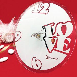 """Bomboniera orologio Love moderno orologio da parete realizzato interamente in vetro bianco, di forma rotonda, lancette argentate e scritta """"Love"""" made in Italy e sono realizzate artigianalment"""